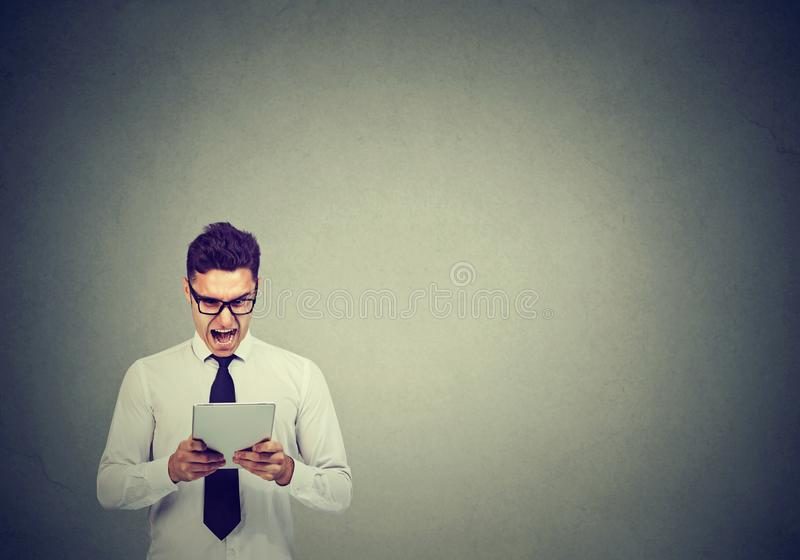 Angry young business man in glasses using a tablet screaming stock photography