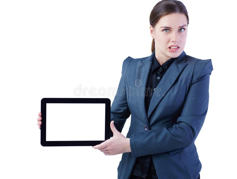 Angry young business woman standing over white background showing display of tablet computer to camera. Focus on her royalty free stock image