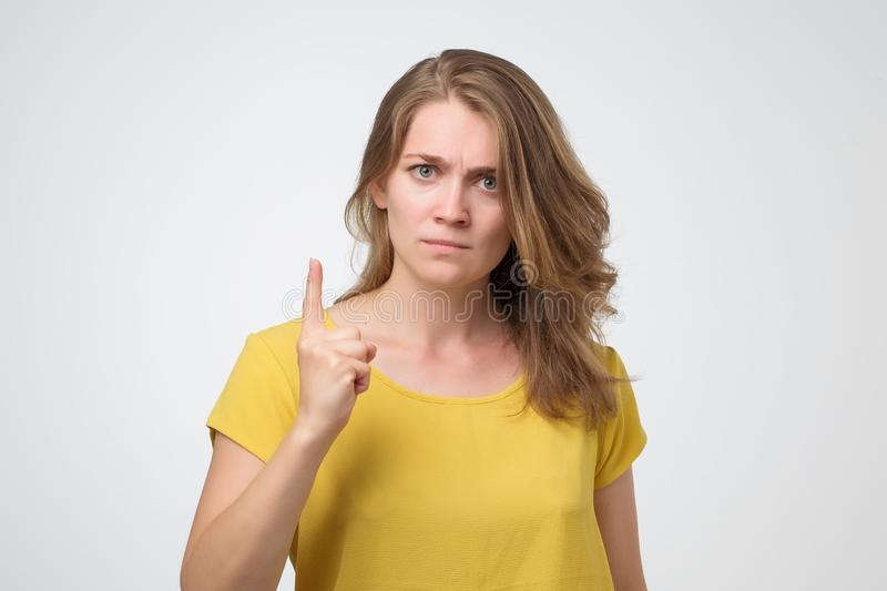 Angry young caucasian woman warning you. It is dangerous royalty free stock image
