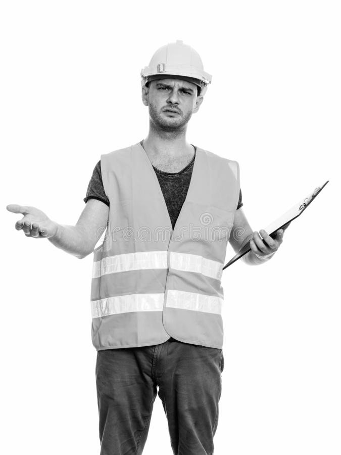 Angry young man construction worker looking confused while holding clipboard. Studio shot of young man construction worker isolated against white background in stock images