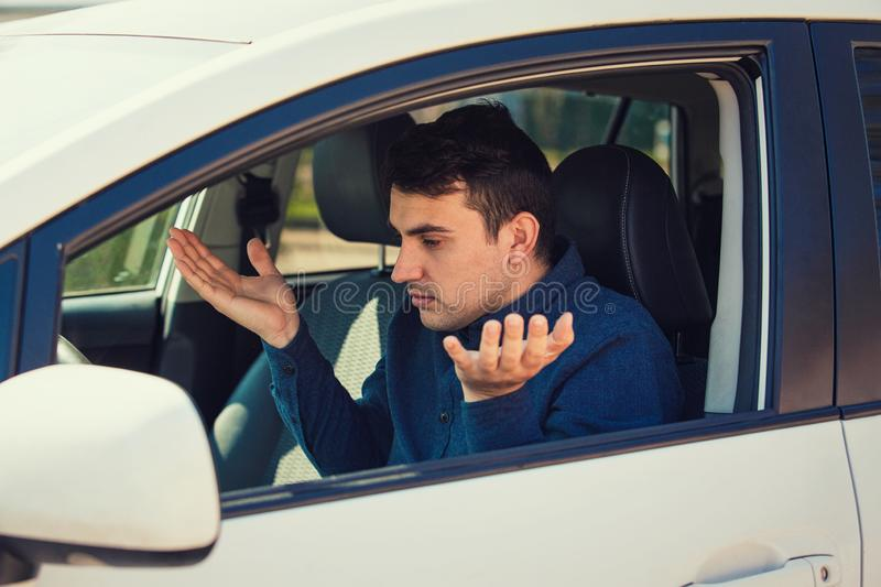 Angry young man driver, pissed off shaking hands and shrugging shoulders, has problems with the car. Displeased perplexed guy has a road accident. Traffic jam stock images