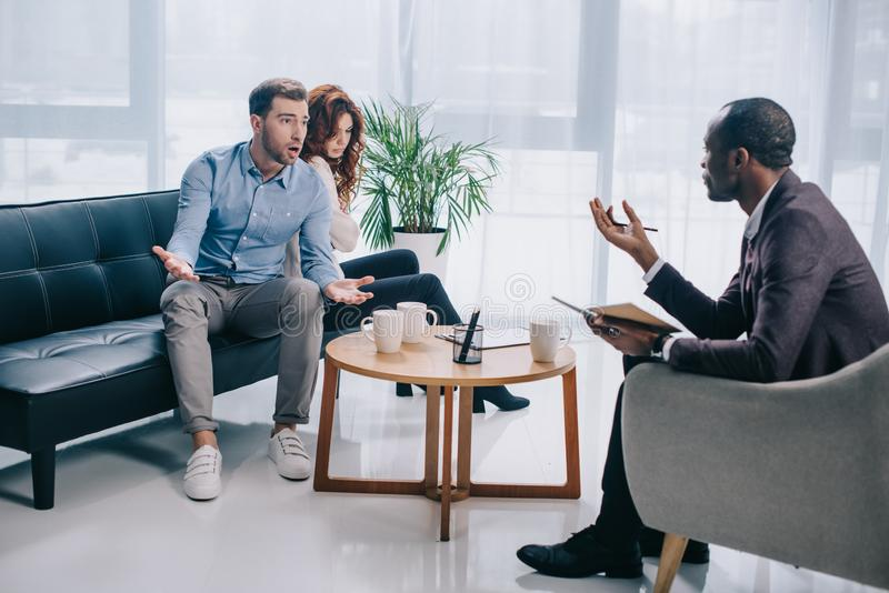 Angry young man with girlfriend sitting on sofa and arguing. With counselor royalty free stock photos