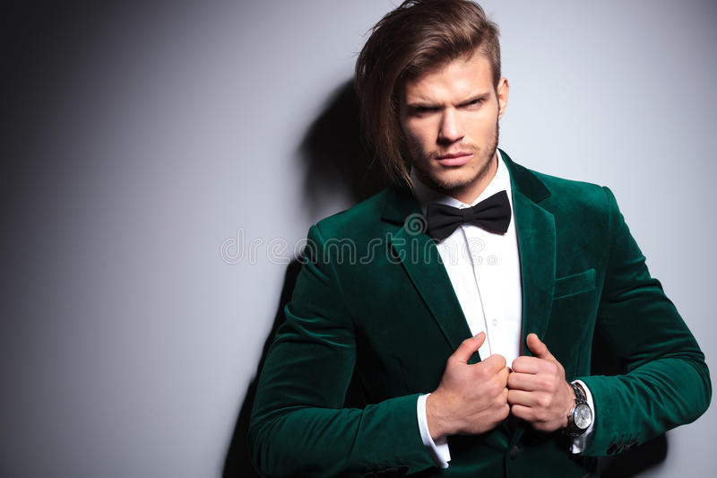 Angry young man in green velvet suit. Looks at the camera on gray background stock photography