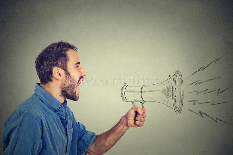 Angry young man holding screaming in megaphone. Portrait angry young man holding screaming in megaphone isolated on grey wall background. Negative face stock photography