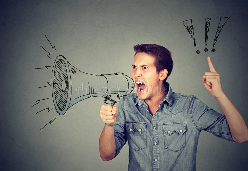 Angry young man holding screaming in megaphone. Side portrait angry young man holding screaming in megaphone on gray background. Negative face expression emotion stock photography
