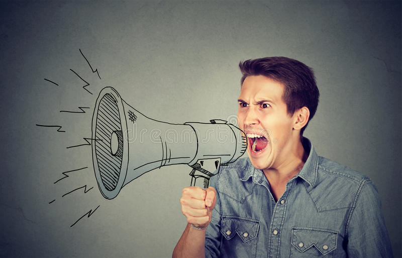 Angry young man holding screaming in megaphone. Side portrait angry young man holding screaming in megaphone isolated on gray background. Negative face stock image