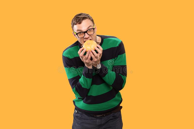 Angry young man holds a pumpkin in his hands and bites it on a yellow background. Studio photo. Angry young man holds a pumpkin in his hands and bites it on a stock images