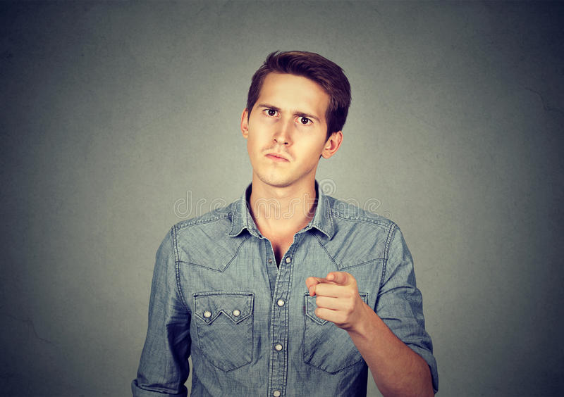 Angry young man pointing finger at you camera stock photography