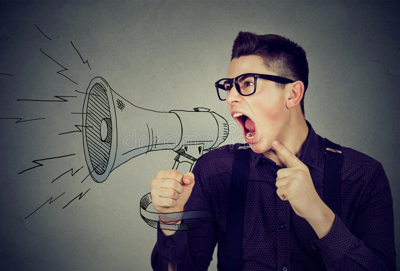 Angry young man screaming in megaphone. Isolated on gray background. Negative face expression emotion feeling. Propaganda, breaking news, power of social media royalty free stock images