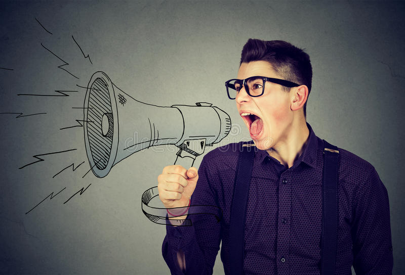 Angry young man screaming in megaphone. Isolated on gray background. Negative face expression emotion feeling. Propaganda, breaking news, power of social media royalty free stock photography