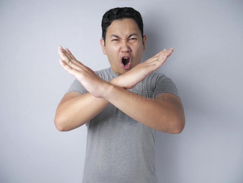 Angry Young Man Shows Stop Sign Crossed Arms gesture royalty free stock photo