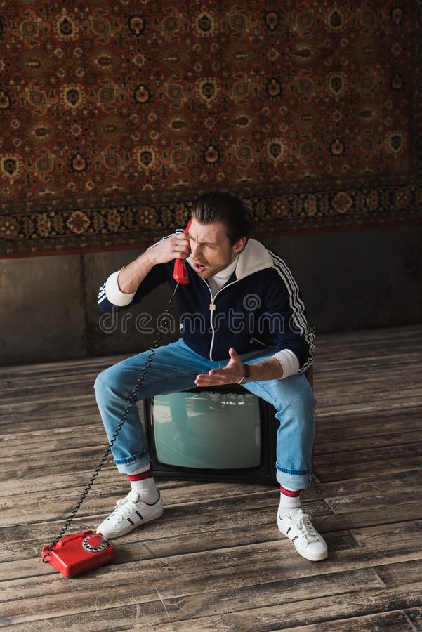 Angry young man in vintage clothes sitting on retro tv set and talking by phone in front of rug hanging. On wall stock image
