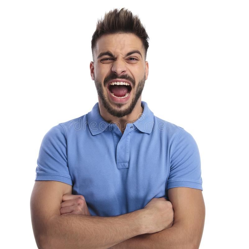 Angry young man wearing a light blue polo shouting out loud. While holding his hands crossed on a ligh backgound royalty free stock photos