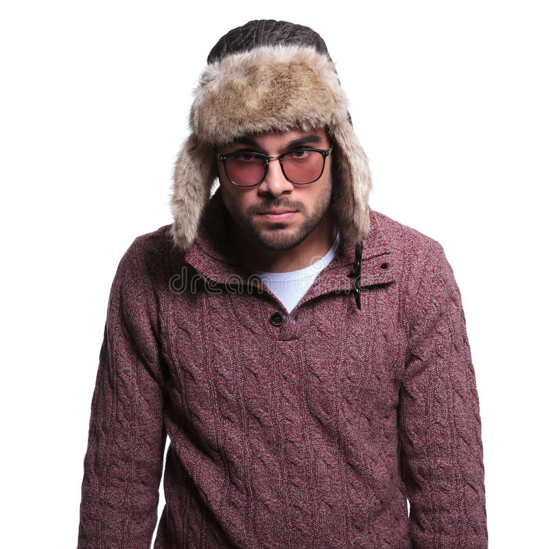 Angry young man in winter clothes and fur hat stock image