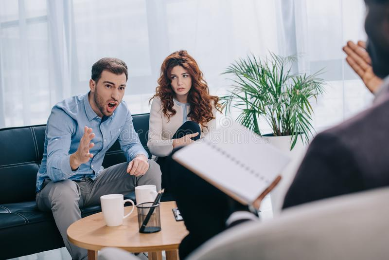 Angry young man with girlfriend sitting on sofa and arguing. Angry young men with girlfriend sitting on sofa and arguing with counselor royalty free stock photography