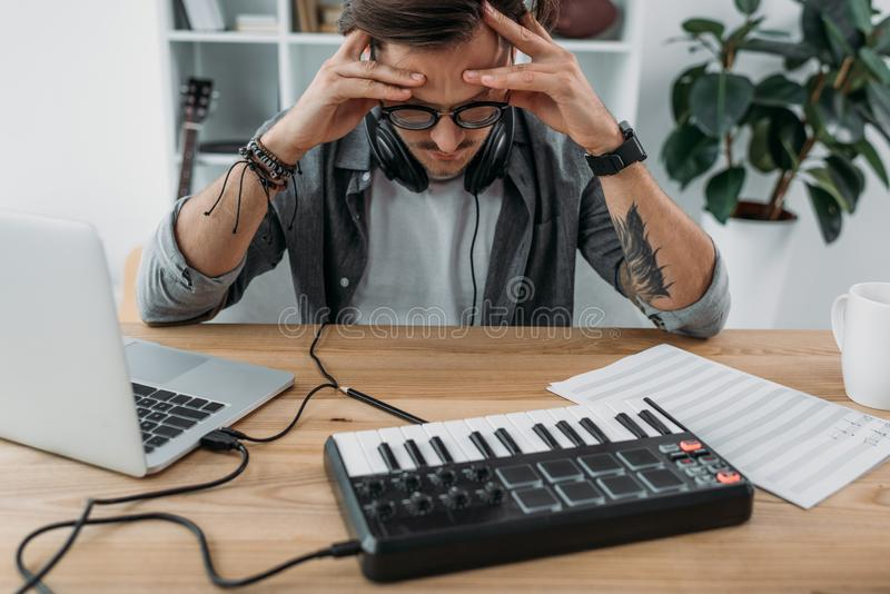 Angry young musician. Depressed young musician having troubles with new project holding head with hands stock photography