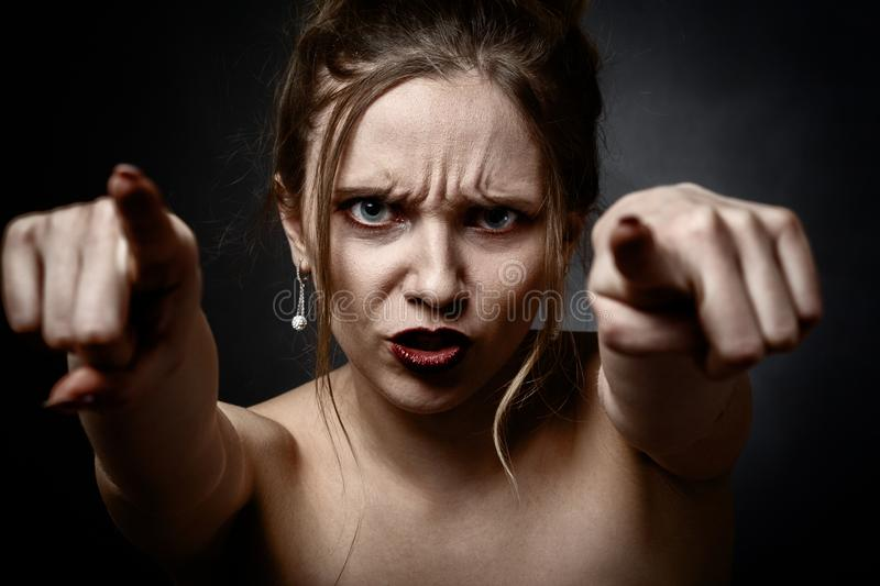 Angry young woman. On black background point on camera royalty free stock images