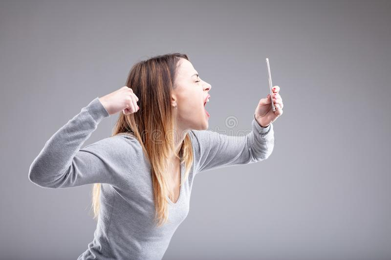 Angry young woman attempts to punch her phone. Single angry young woman attempts to punch her phone as she takes picture with it in front of plain grey stock photo
