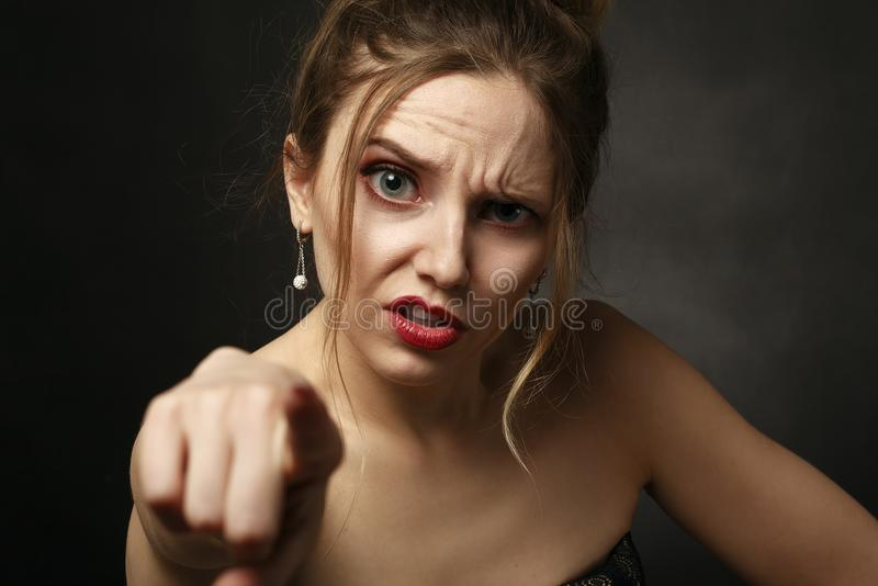 Angry young woman. On black background point on camera stock photo