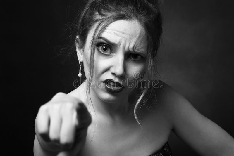Angry young woman. On black background point on camera, monochrome royalty free stock photo