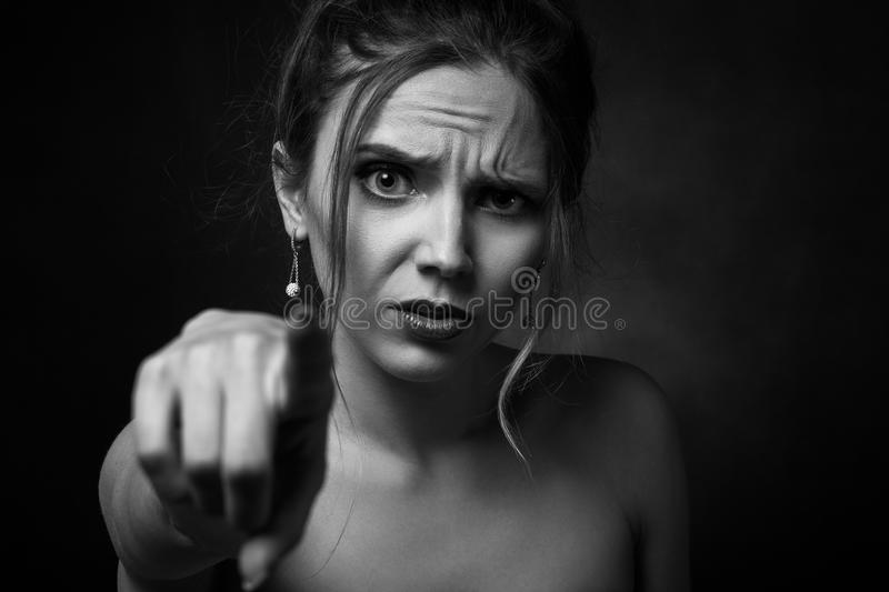 Angry young woman. On black background point on camera, monochrome stock photos