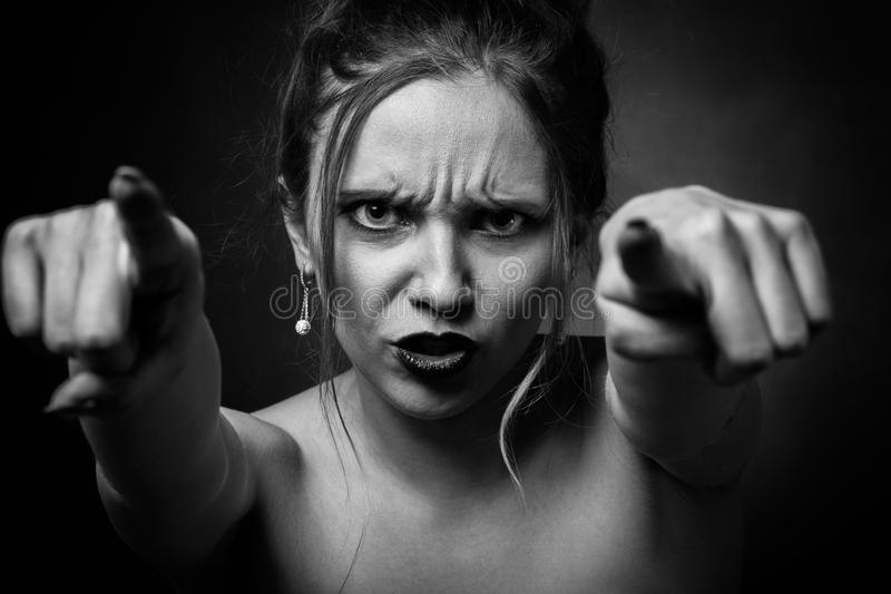 Angry young woman. On black background point on camera, monochrome royalty free stock photography