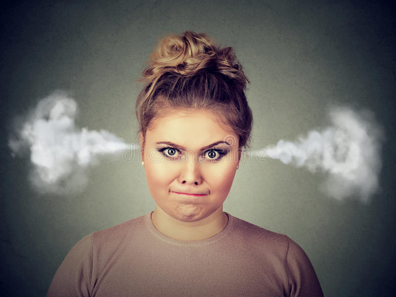 Angry young woman, blowing steam coming out of ears. Closeup portrait of angry young woman, blowing steam coming out of ears, about to have nervous atomic royalty free stock photography