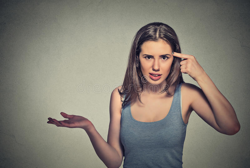 Angry young woman gesturing asking are you crazy?. Closeup portrait of angry mad young woman gesturing with her finger against temple asking are you crazy? royalty free stock photos