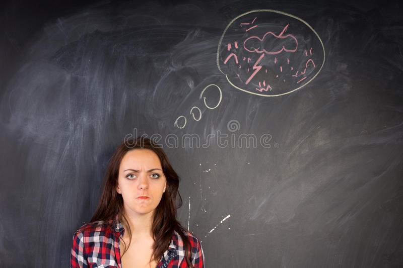 Angry young woman glaring at the camera. In a depiction of rage as shown by the hand-drawn diagram of a bolt of lightning and thunder on the chalkboard stock images