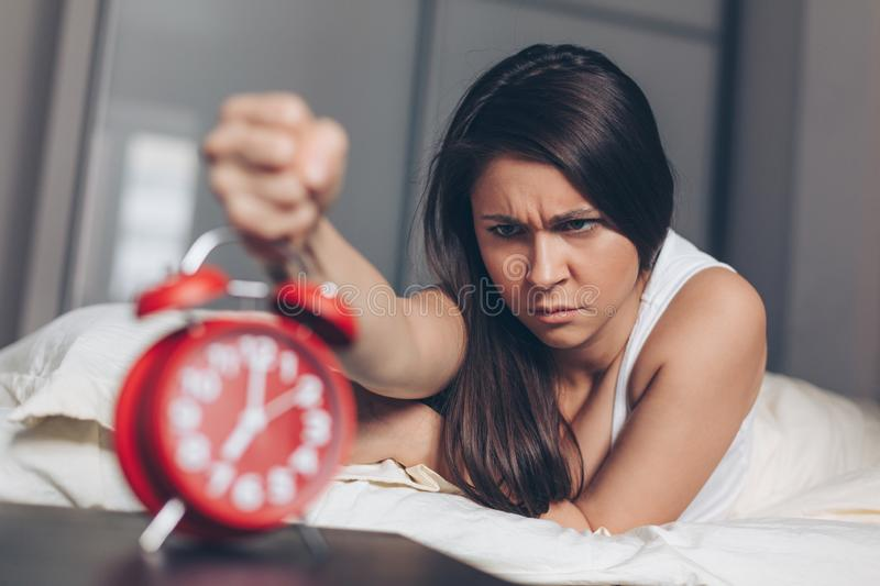 Angry young woman kill off alarm clock by fist on the bed in the morning stock photos
