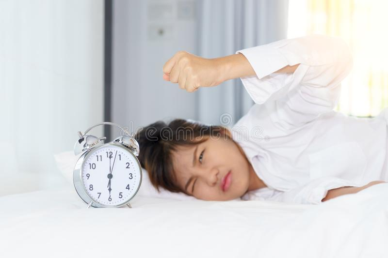Angry young woman looking at alarm clock with clench one`s hand royalty free stock image
