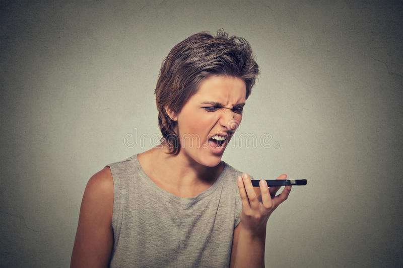 Angry young woman screaming on mobile phone. Portrait angry young woman screaming on mobile phone isolated on gray wall background. Negative emotions feelings stock photography
