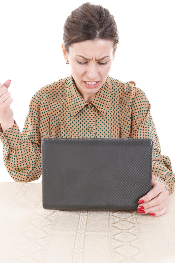 Angry young woman in shirt sitting and using laptop royalty free stock photo