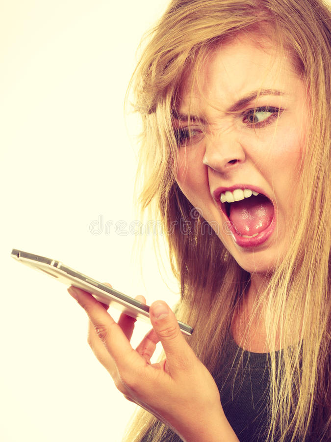 Angry young woman talking on phone. Unpleasant conversation, bad relationships concept. Screaming furiously angry young blonde woman talking on phone stock image