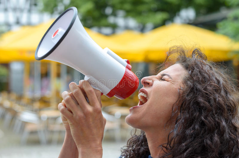 Angry young woman using a loud hailer. Or megaphone outdoors in an urban square during a protest or demonstration stock photography