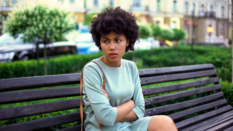 Angry young woman waiting for boyfriend on bench, romantic date in city, love royalty free stock image