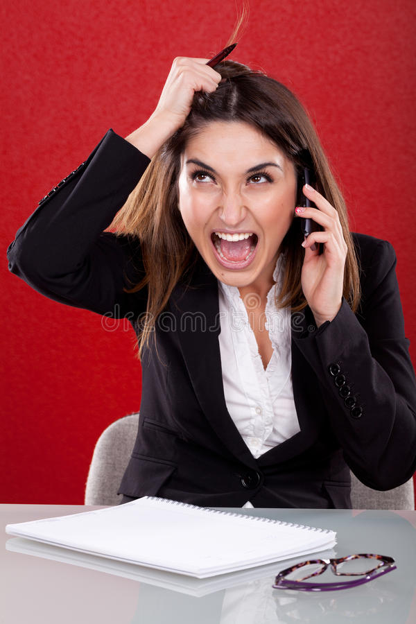 Angry young woman at work royalty free stock photo