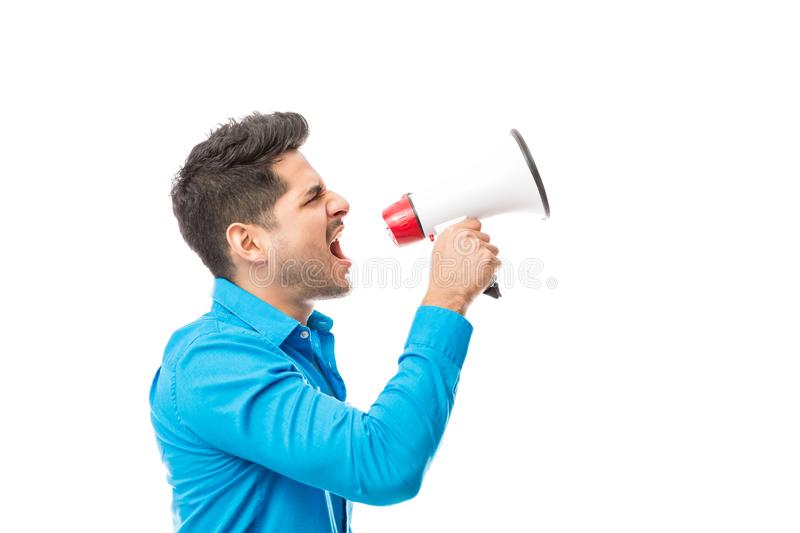 Angry Youth Protesting While Using Megaphone. Side view of angry youth protesting while using megaphone against white background royalty free stock photography