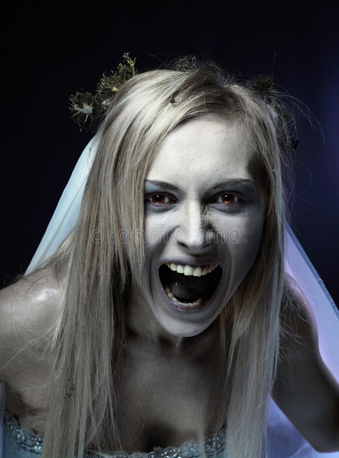 Angry zombie corpse bride. Portrait of angry zombie corpse bride looked scary and standing at dark background. shot in studio royalty free stock photos