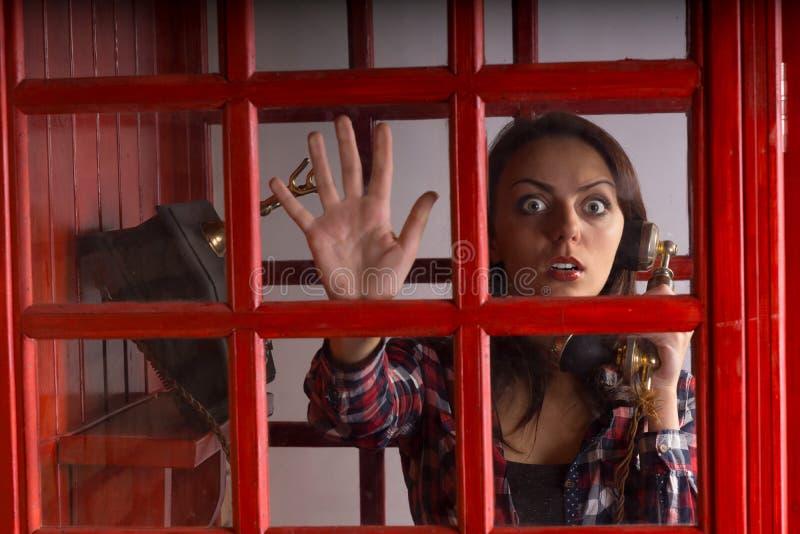 Angst aangejaagde die vrouw in een telefooncel wordt opgesloten royalty-vrije stock foto's