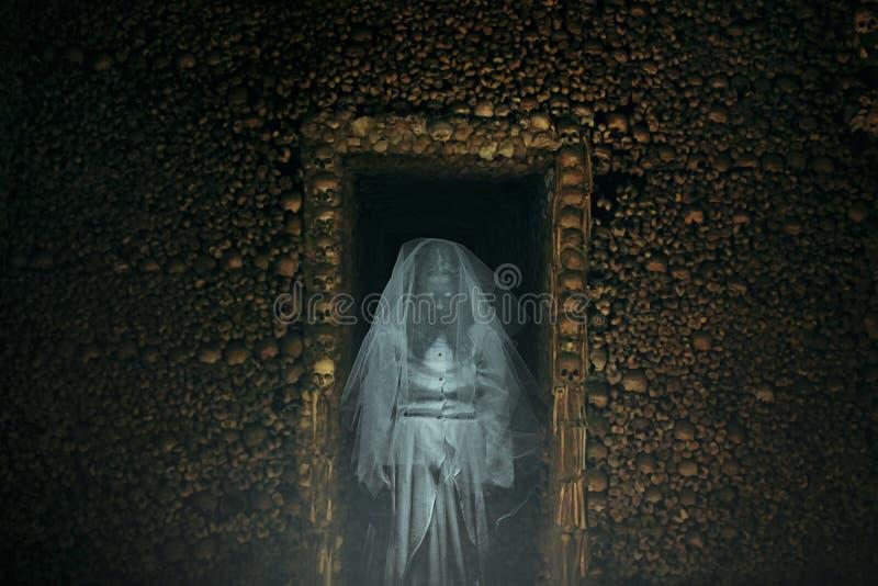 Angstaanjagend spook in een catacombehoogtepunt van beenderen stock foto