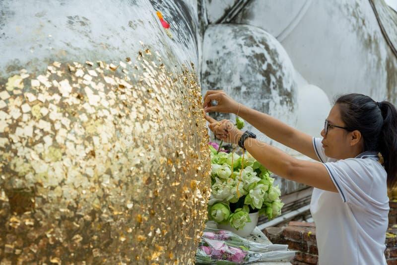 Angthong/Thailand - Mei 29 2018: hand van vrouwen of boeddhistisch gilde door bladgoud op messing Boedha, in Thailand stock afbeeldingen