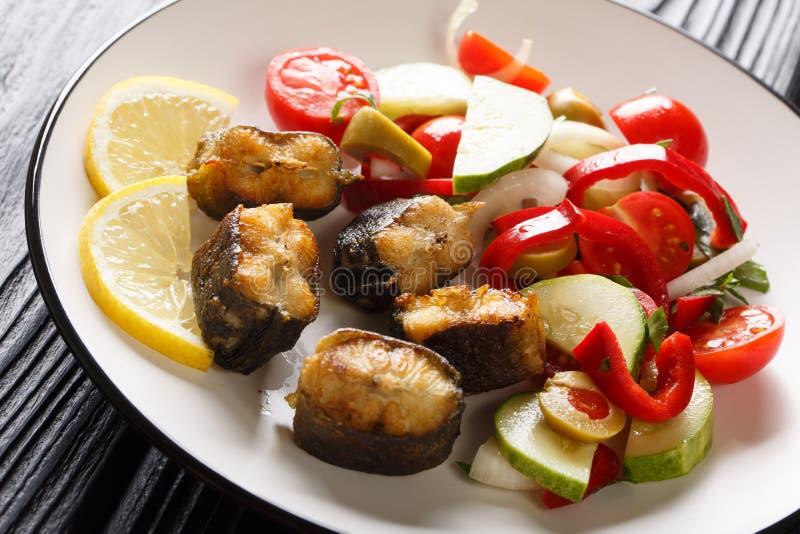 Anguila frita de la comida gastrónoma con el primer de la ensalada de las verduras frescas en una placa horizontal imagen de archivo