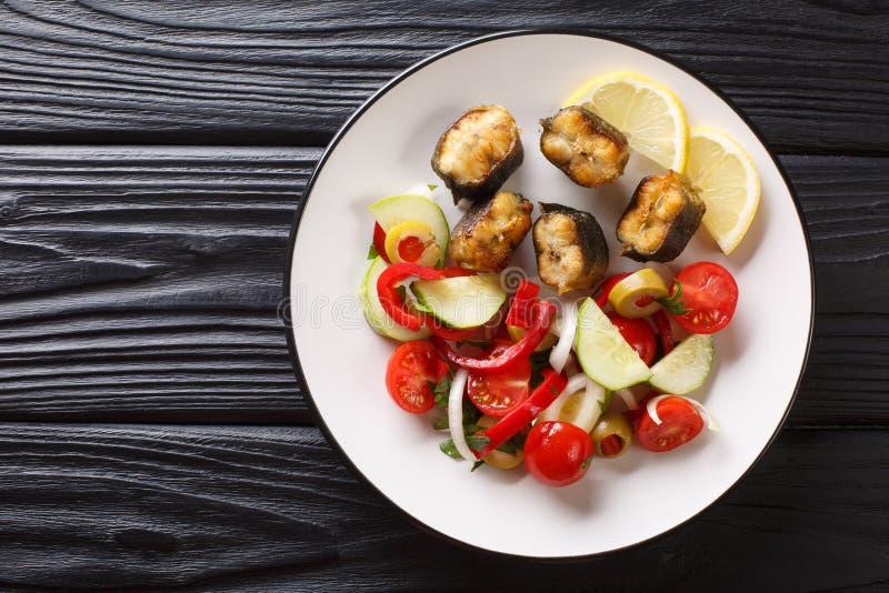 Anguila frita de la comida gastrónoma con el primer de la ensalada de las verduras frescas en una placa visi?n superior horizonta foto de archivo libre de regalías
