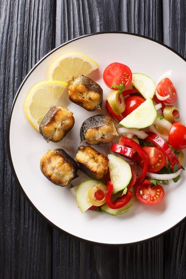 Anguila frita de la comida gastrónoma con el primer de la ensalada de las verduras frescas en una placa Visi?n superior vertical imagenes de archivo