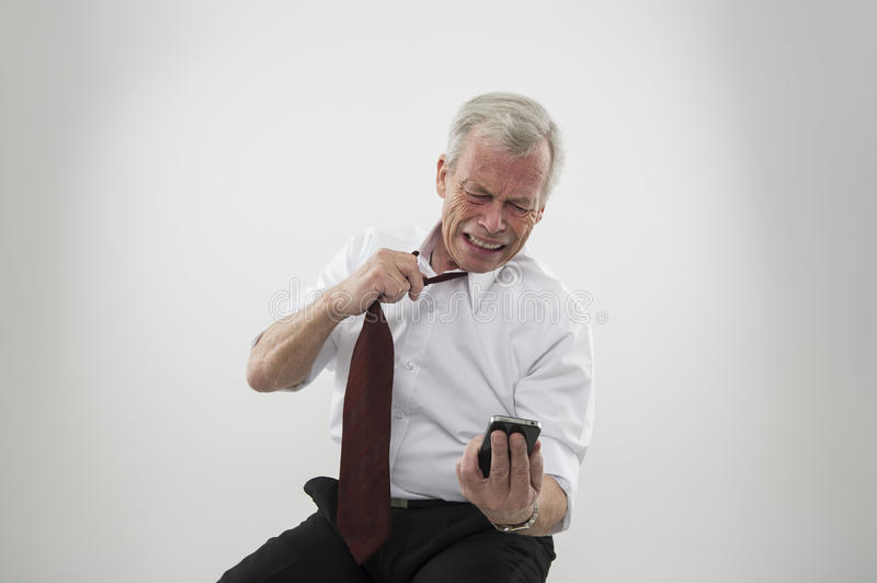 Anguished man reading a message on a mobile. Anguished senior gey-haired man loosening his tie reading a message on the screen of his mobile phone reacting with stock photo