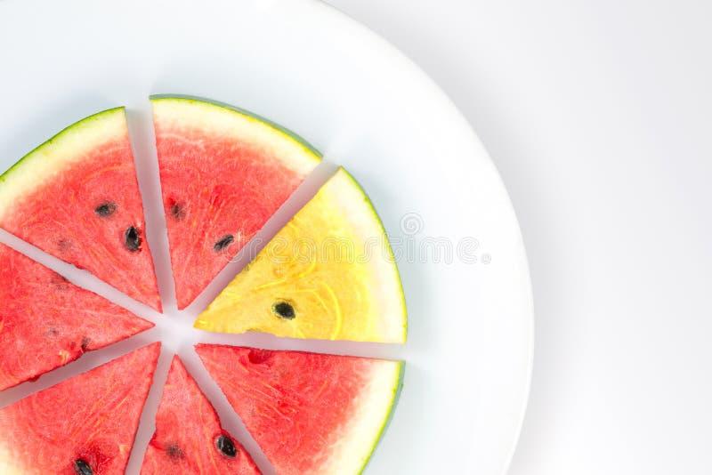 Anguria rossa e giallo affettato sul piatto bianco fotografia stock libera da diritti