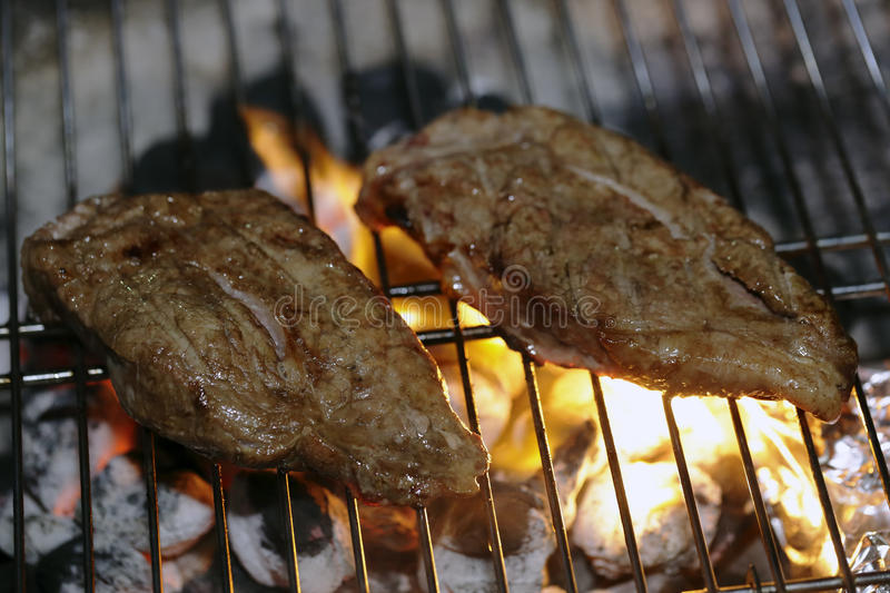 Angus steaks on a barbecue. Aberdeen Angus striploin steaks cooking on a barbecue stock photo