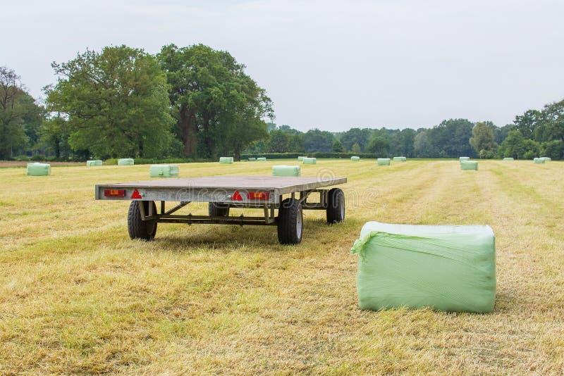 Anhänger in der Rasenfläche mit plastifizierten Heuballen lizenzfreies stockfoto