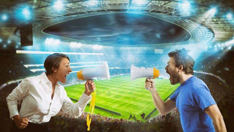 Anhänger von gegenüberliegenden Teams schreien gegeneinander mit einem Megaphon am Stadion während eines Fußballspiels stockbild